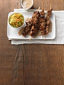 Satay skewers with a cashew and peanut sauce and a sweet and spicy coleslaw