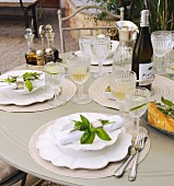 A festively laid garden table with bunches on herbs as napkin decorations