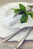 A white place setting decorated with a bouquet of herbs