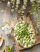 Tarte flambée with asparagus, peas and bacon on a table outside