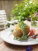 Baked potato with herb sauce outside on a garden table