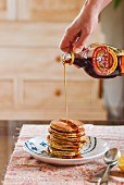Maple syrup being poured onto a stack of pancakes