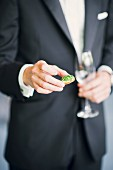 A bride groom holding a canapé and a glass of champagne