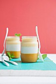 A layered dessert with mango, coconut and pineapple cream