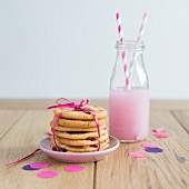 A stack of strawberry biscuits tied with ribbon with a strawberry drink
