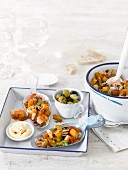 Seafood tapas with crispy potatoes, olives and aioli