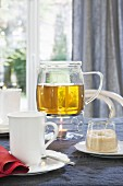 Herb tea in a glass pot on a warmer with a sugar pot and a cup