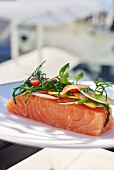 Raw salmon fillets topped with a bouquet of vegetables