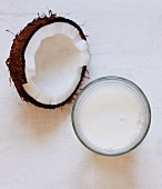 Half a coconut and a glass of coconut milk