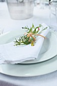 A white napkin with a delicate bouquet of herbs