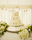 White wedding cake surrounded by bouquets