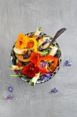 Pepper and courgette salad with nasturtium flowers, borage flowers, rosemary and chilli