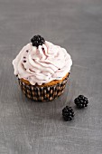 A cupcake with blackberries and blackberry cream
