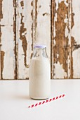 A bottle of cashew nut milk with a straw next to it