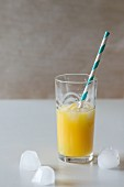 A glass of orange juice with ice cubes and a retro straw