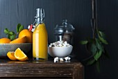 A bottle of orange juice, fresh oranges and popcorn