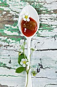 Strawberry and rhubarb jam on a spoon with strawberry leaves on a wooden table