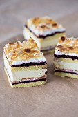 Three slices of almond cream cake with blackcurrant jam and flaked almonds