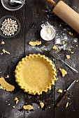 Shortcrust pastry dough pricked with a fork in a baking tin