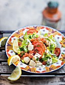Warm fish and potato salad with tomatoes, lemons and coriander