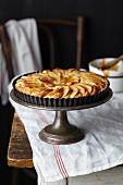 A whole apple and frangipane tart glazed with apricot jam on a cake stand