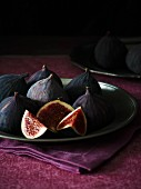 Fresh red figs on a plate, one sliced