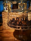 Chocolate confectionery under a glass cloche