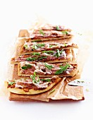 Slices of pancetta and rocket pizza