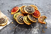 Colourful herb, olive and tomato spiral pastries with Parmesan