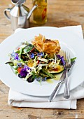 A goat's cheese filo pastry served with salad with herbs and edible flowers