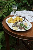 Fried plaice with garlic and rosemary potatoes, lemons and fresh parsley
