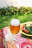 Ein Pils im Glas auf Gartentisch daneben sommerlicher Salatteller