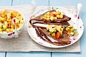 Chocolate pancakes with vanilla cream and peach salsa