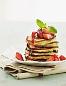 A stack of pancakes with fresh strawberries