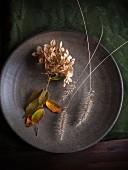 Herbstliche Hortensienblüte und Gräser auf Teller (Draufsicht)