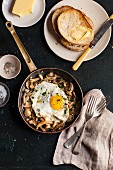 Fried mushrooms with a fried egg in a pan served with toast and butter