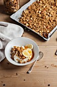 Granola with nuts and honey on a baking tray with a bowl of yoghurt muesli and banana in the foreground
