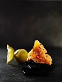 A piece of salmon with sesame seeds on a slate platter with lemon wedges behind it