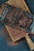 Grated dark chocolate with grater and piece of chocolate