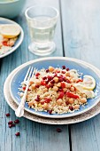 Couscous with chick peas, roasted peppers, pomegranate seeds and cumin