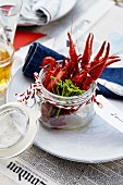 A place setting with cooked crayfish in a jar