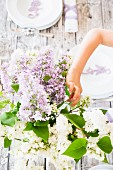 Person decorating spring dining table with vase of lilac