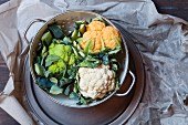 Various different coloured cauliflowers on a pewter plate