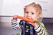 A little girl biting into a large carrot