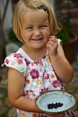 Cheerful girl wearing floral summer dress holding vintage plate of blackcurrant