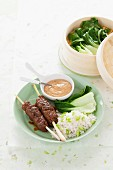 Minced meat skewers with rice, bok choy and peanut sauce (India)