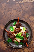 Venison skewers with cinnamon on a bed of celery cream