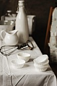 White Paper cases and an old whisk on a table