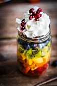 A colourful fruit salad in a jar topped with cream and pomegranate seeds