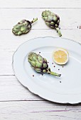 Fresh baby artichokes, half a lemon and pink peppercorns on a porcelain plate